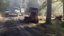 Cottage in the woods - the construction of the road with bulldozers and trucks.