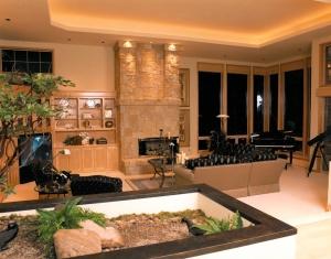 Example of custom interior lighting around the masonary of a fireplace and an inside garden.