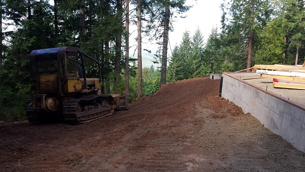 Bulldozer spreads the dirt on the landscape of New Cottage in the Woods.