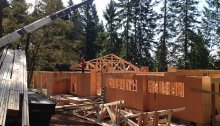 Crane lifts roof trusses on top of New Cottage in the Woods