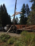 The Crane truck lifts a roof truss onto the top of New Cottage in the Woods