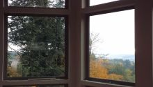 View of the main windows in the living area overlooking the Tualitin Valley- New Cottage in the Woods.